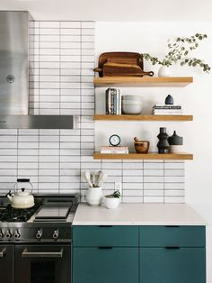 White Glazed Brick 2x8 Subway Tile from Fireclay with Painted Green Kitchen Cabinets and Floating White Oak Shelves. Matte Black Hardware and Stainless Steel Range and Appliances. Our Austin Casa || The Kitchen Reveal - The Effortless Chic