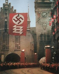 Crowds of Germans line the streets, with ceremonial torches burning and a large German flag, accompanied with traditional Wolfsangel symbols, hangs above the Old Rathaus on the Marienplatz, Munich. November 9, 1938.