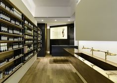 Aesop's Hollywood Road store features pale oak, copper and blackened steel - Botellas ambar y repisas de madera clara
