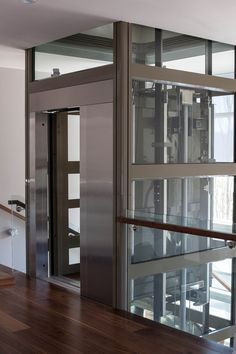 Garaventa Lift Home Page. We produce and install home elevators, inclined and vertical platform lifts, stairlifts in the USA, Canada and Mexico. Elevator Lobby Design, Living Room Designs, Living Spaces, Glass Lift, Glass Elevator, Lift Design, House Elevation, Under Stairs, Cladding