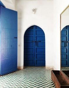 Blue arched doors and chevron flooring