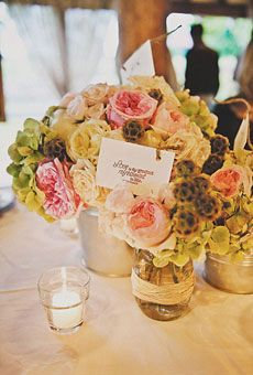Centerpieces of scabiosa pods, hydrangeas, and garden roses arranged in mason jars and tin pails. Photo by Kyle Hale. Flowers by Gloriosa Design