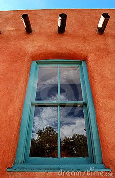 Old adobe building located in Santa Fe, New Mexico with a turquoise window.