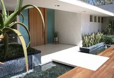 Door Zen-try — This gorgeously landscaped home in Encino Hills features an elegant wooden door flanked by panes of translucent glass, and a simple inset bridge over a placid river rock stream.