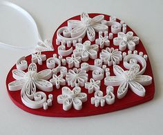A Quilled / Filigree Deep Rich Red Heart Accented in Bright White Flowers with Swirls, Curls and Dots. A Hanging Decorative Heart.