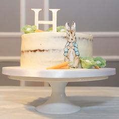 Semi naked carrot cake with hand painted sugar Beatrix Potter Peter Rabbit, gold hand cut and hand painted H sugar topper and sugar vegetables. Photo by Laurence Smith