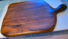 My favorite and well-worn walnut cutting board...the unusual thing is that the handle is thicker than the cutting board, giving it a sort of sculptured look. My kids have been reluctant to use them for cutting, but they are intended to e used, of course.