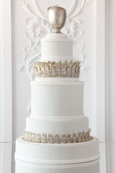 A simple white cake is wrapped in gilded leaves and topped with a hand-made golden apple.
