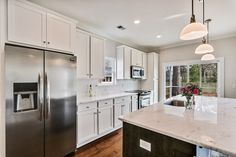 White exterior wall cabinets.  Dark gray island cabinets.  White granite.