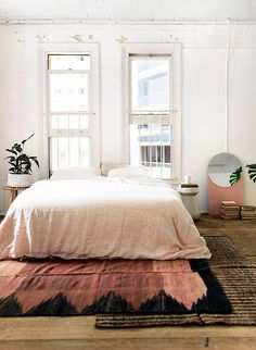 Layer rugs with complementary patterns and textures to achieve that perfect bohemian look in your bedroom