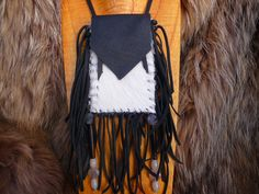 This is a nice contrasting Medicine Bag made from Black Deerskin leather, and decorated with White African Springbok fur. Soft Leather Tassels decorate the sides of this piece, and have 2 beaded tasse
