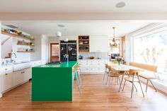 Cozinha com piso de madeira, bancada verde e armários brancos. Mesa de madeira com pés metálicos. Cozinha Verde Greenery e outros tons!