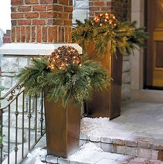 Lit pine cone bouquet in evergreens atop tall copper vases makes for beautiful holiday curb appeal.