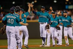 Members of the Seattle Mariners celebrate after defeating the New...