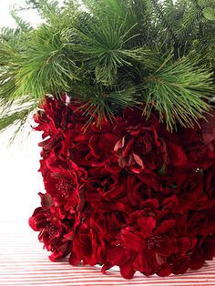 Make a vase filled with evergreens even more stunning by covering it with fresh flowers to make a simple and festive centerpiece for the holidays.