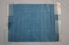 "The before conservation image of a land survey/blueprint plot map. The map had been stored rolled for many years. The exposed edges had tears and the paper had a strong ""memory"" of being rolled. The paper had also become quite brittle. After being conserved at Spicer Art Conservation, the map was framed using archival materials, including UV filtering plexiglas. The frame was sealed to prevent dust, debris or other contaminants from entering."