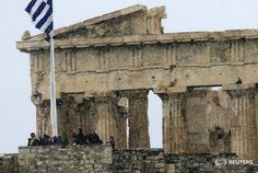 Tourists take photos atop the Athens Acropolis during a snowstorm February 10, 2015
