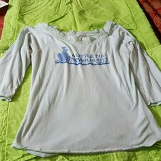 Baby blue Guess top Cute top with A LITTLE TUG NEVER HURTS written on it with a pic of a tugboat and rhinestone trim. The wide neck is trimmed in lace and the sleeves are 3/4 length. T-shirt material and 100% cotton. Guess Tops