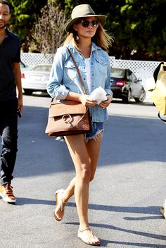 Chrissy Teigen wearing denim cutoffs, a chambray shirt, and a floppy brim fedora