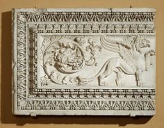 Architectural panel with a griffin Roman, Imperial Period, about A.D. 175–200. An eagle-griffin stands with one paw raised and the central element was probably a candelabrum. The griffin's tail turns into a rich acanthus vine, which sends out a lateral shoot and terminates in a cluster of leaves. The frame consists (from inside out) of an astragal, a row of acanthus leaves with intervening leaf tongues, a Lesbian cymation, and an astragal.