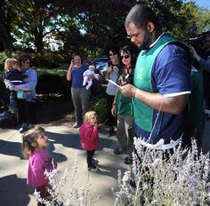 Patriots defensive lineman Ron Brace towers over Penelope Lade, 3, of Upton as he signs an autograph for her while helping the Greenleaf garden Club spruce around the Milford Public Library .