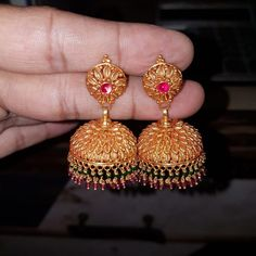 Stunning gold antique jumkhis studded with pink color stones. Jumkhis with green and pink color bead hangings. Gold Jhumka Earrings, Jewelry Design Earrings, Gold Earrings Designs, Gold Jewellery Design, Necklace Designs, Pendant Jewelry, Jewelry Sets, Gold Necklace, Gold Jewelry Simple