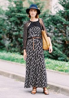 A floral print maxi dress is worn with strappy flats, a tote bag, and blue fedora