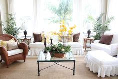 Love the slipcovers mixed with the rattan chairs and rug