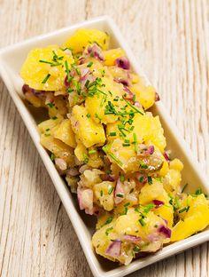 Bayrischer Kartoffelsalat garniert mit Schnittlauch in weißer, rechteckiger Porzellanschale in der Vogelperspektive