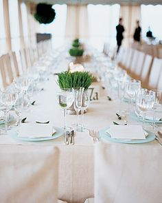 Centerpieces of wheat grass in pewter cachepots pop against an all-white table.