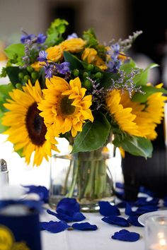 Spring wedding decor: Sunflower centerpiece surrounded by blue rose petals