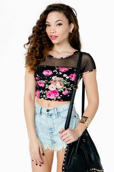 A totally rad 90's inspired crop top featuring a vibrant floral print and a sheer mesh inset. Round neck. Short sleeves. Finished hem. Knit. Light stretch fit. Looks amazing with frayed cutoffs and combat boots.