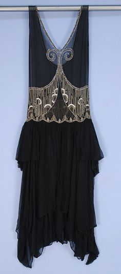 DECO BEADED CHIFFON OVER-DRESS, 1920's. Black silk with V-neck and U-back, having rhinestone and silver beaded neckline, front scrolls and midriff band, full skirt split at center front, eneven hem folded into side panniers.