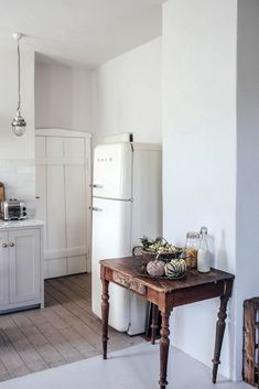 A Smeg fridge is tucked in the back, next to doors to the dining room and WC. The existing flooring was preserved and upgraded: it's a combination of old wood (newly finished with gray linseed oil) and painted concrete. Shaker Kitchen, Rustic Kitchen, Kitchen Decor, Ikea Kitchen Lighting, Kitchen Kit, Cottage Kitchens, Home Kitchens, Countryside Kitchen, Country Look