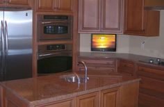 Kitchen With Wooden Cabinets And LCD TV