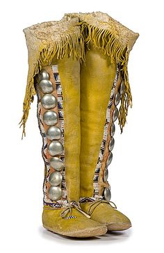 Kiowa girl's beaded hide hightop moccasins -  Thread-sewn and beaded using dark blue, rose, greasy yellow, and white; each with nine German silver buttons; hide coated with yellow and red pigment, length 9.25 in. x height 23 in. late 19th century