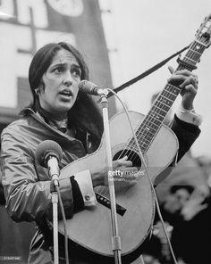 Singer Joan Baez strumming guitar during protest march in Trafalgar...