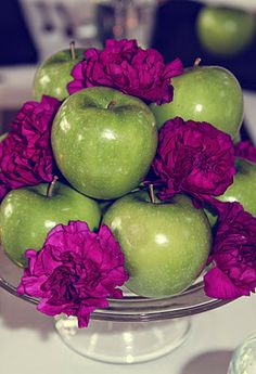 Simple centerpiece with apples and flowers piled on a cake stand.