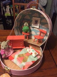Diy suitcase dollhouse. Cardboard suitcase is from Ross $4, wood furniture is from Dollar Tree $1 each, wall frame from Michaels $1.50 pack. I painted outside of box, decoupaged the inside, painted furniture, sewed blanket and pillow. Perfect for Calico Critters!