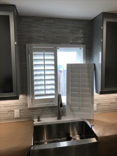 Kitchen window with removable doors plantation shutter due to over size sink faucet by Elite Decor Miami