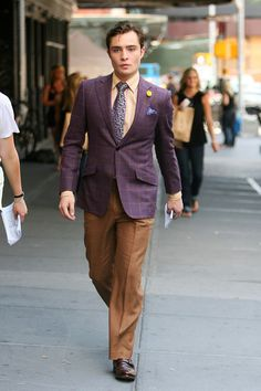 Ed Westwick, wearing a purple blazer, multi-colored striped dress shirt and brown slacks, as he walks to the set of Gossip Girl in New York City.