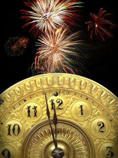 Close up of the minute hand of a antique clock face about to strike 12 o-clock midnight to start the new year with fireworks in the background. Stock Photo
