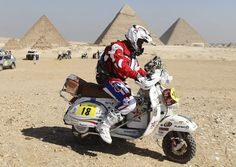 Andrea Revel Nutini of Italy prepares to race on his Piaggio Vespa PX150 bike at the start of the International Cross Country Rally of the Pharaohs at the Pyramids Plateau in Giza.