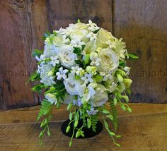 Bridal bouquet ..inspired by Kate Middleton.  This one didn't cost nearly as much as hers!   Featuring giant white freesia, Stephanotis, Dendrobium orchids and white 'Polo' roses, accented with Boston fern tips.. the illusion is the inverted teardrop or as the British describe it, Shield bouquet.  Perfectly balanced.