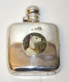 A SILVER HIP FLASK, Birmingham 1919, with oval enamel dog portrait.