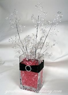 """This is soooo cute!  And diy! """"A reception centerpiece wrapped in black satin ribbon and accented with a circular rhinestone buckle. Pink faux ice fills the vase and rice bead sprays were used instead of flowers. This design can be adapted to a spring or winter wedding."""""""