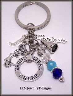 This is an adorable Silver plated dangle Cheer-leading Key-chain, comes with 5 charms. 1 Circle Cheer charm, silver megaphone charm, Cheerleader word silver charm, Initial of your choice, cheerleader with pom poms charm,& blue & white beads. Ready for gift giving. What a fun Cheer-leading charm Key-ring great for any cheerleader. Makes a great gift idea. Your Cheer-leading Key-chain will come to you in a pretty organza gift bag, ready for gift giving. Ideal for Banquets, End of year gifts…