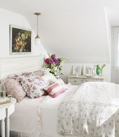 Floral accents, such as throw pillows, a comforter, and fresh flowers in a vase add a feminine touch, like in this New York beach house. - CountryLiving.com