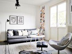 tapis en gris clair à motifs blancs et un canapé en gris foncé dans le salon