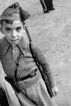 "Photo by Robert Capa. Spanish Civil War, Barcelona The boy is wearing a cap of the Steel Battalions, of the ""Union de Hermans Proletarios"" (Union of Proletarian Brothers), an anarchist militia."